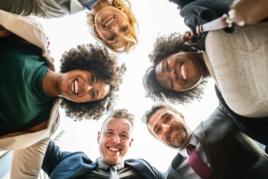 Engaged employees smiling in huddle image
