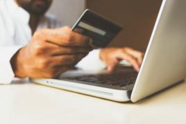 Man typing bank card number on laptop image
