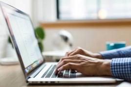 Man writing a marketing plan on laptop image