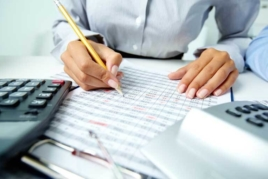 Woman calculating vat at office desk image