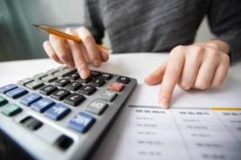 Woman typing on calculator doing tax return image